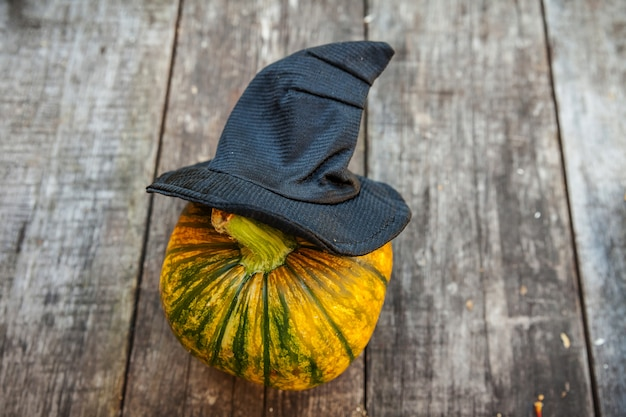 Jack o lantern halloween-pompoen met zwarte heksenhoed op houten achtergrond. halloween party concept. vakantie seizoen groet, trick of treat spookachtig.