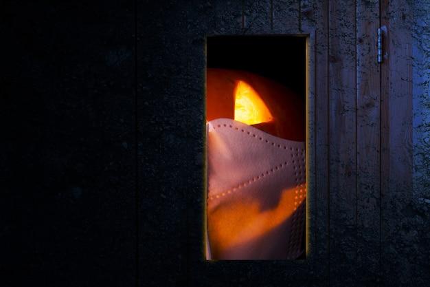Jack-o-lantern in gezichtsmasker achter de deur met donkere achtergrond