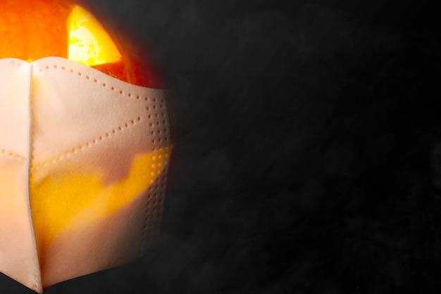 Jack-o-lantern in het gezichtsmasker met een zwarte achtergrond