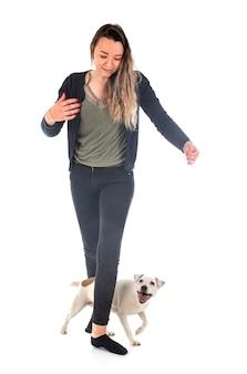 Jack russel terrier en vrouw voor witte muur