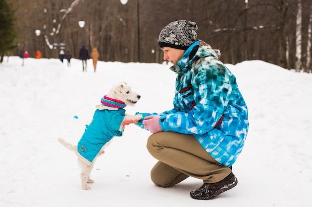 Jack russell terrier hond met eigenaar vrouw spelen in de winter buiten.