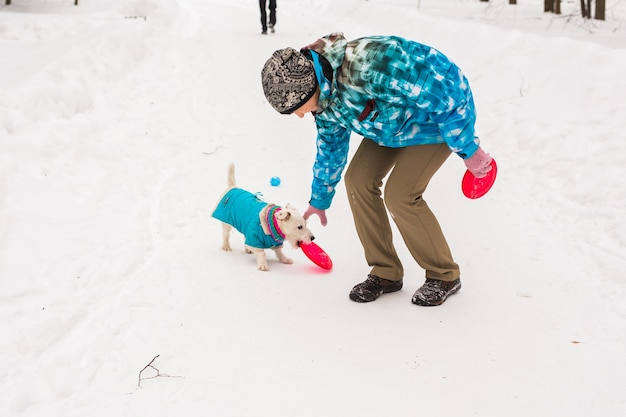 Jack russell terrier hond met eigenaar vrouw spelen in de winter buiten