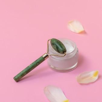 Jade roller gezichtsmassage met gezichtscrème op pastelroze achtergrond met witte bloemblaadjes
