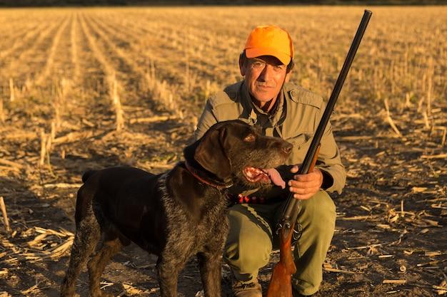 Jager man in camouflage met een pistool tijdens de jacht op zoek naar wilde vogels of wild. herfst jachtseizoen.