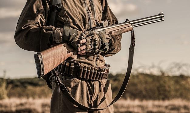Jager man. jachtperiode, herfstseizoen. een jager met een jachtgeweer en jagen