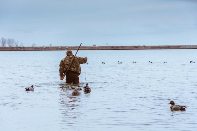 Jager met een geweer op zijn rug tijdens het jagen en het vangen van een vis in het meer met eenden