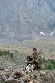 Jager met twee honden die tegen de achtergrond van een berg zitten