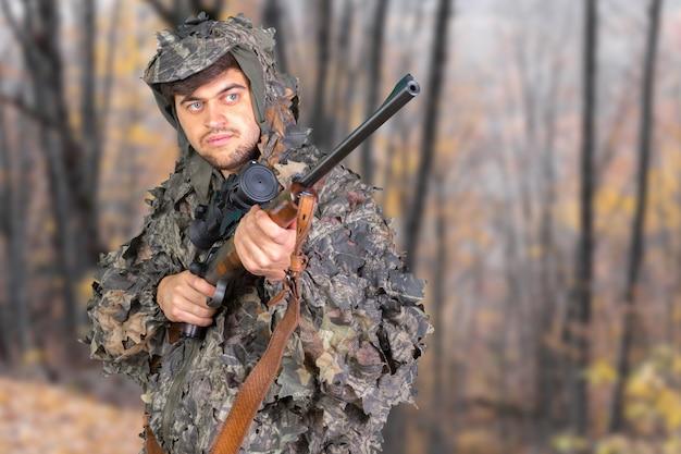 Jager met zijn geweer in een bos