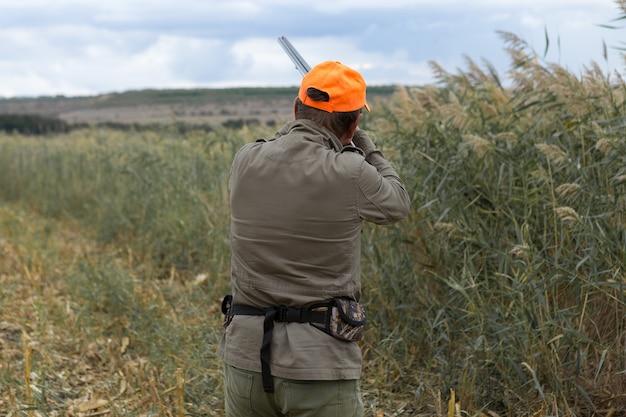 Jagerman in camouflage met een pistool tijdens de jacht op zoek naar wilde vogels
