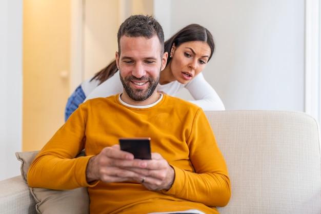 Jaloerse vriendin probeert naar de smartphone van zijn vriend te gluren, voelt zich verdrietig als hij met iemand sms't