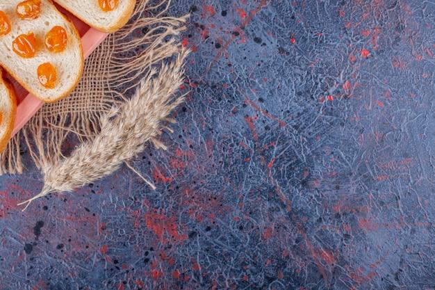Jam op gesneden brood aan boord op jute servet naast materiaal op blauw.