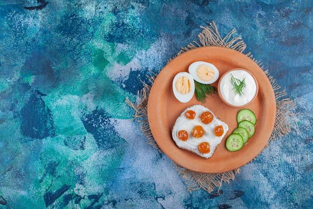 Jam op gesneden brood naast gesneden ei, komkommer op een bord op jute servet, op het blauw.