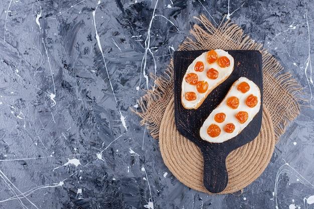 Jam op gesneden brood op een snijplank, op een onderzetter, op de blauwe achtergrond.