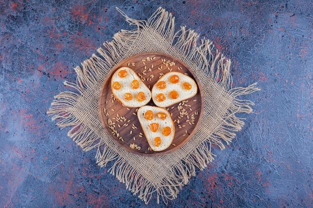 Jam op gesneden brood op houten plaat op handdoek, op blauw.