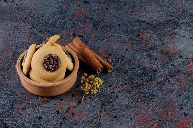 Jam-ringkoekje in een kleikom met kaneelstokjes en mimosabloem