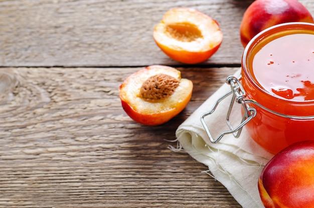 Jam van perziken en nectarines in een pot met vers fruit op een houten tafel.