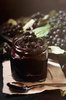 Jam van zwarte appelbessen (aronia-melanocarpa) en zijn bessen op donkere tafel. zelfgemaakte jam.