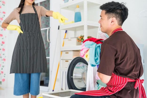 Jammer dat aziatische jongeman van bazige huisvrouw eist om zelf vuile kleding te wassen. huishoudelijk karwei door man terwijl luie vrouw zijn werk controleert.
