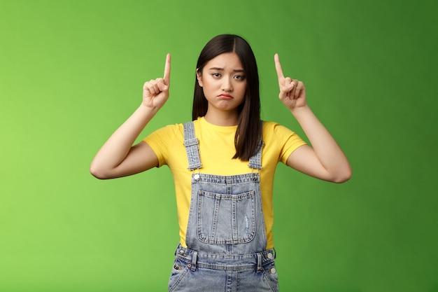 Jammer schattig triest aziatisch meisje brunette, grimassen trekken verdriet overstuur gezicht fronsen gehinderd, wijzende vingers omhoog spijt vreselijke situatie, geven top promo aan, staan groene achtergrond ongelukkig