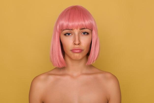 Jammerende jonge aantrekkelijke roze harige vrouw met kort kapsel die droevig naar de camera kijkt en haar lippen pruilt terwijl ze met blote schouders over mosterdmuur staat