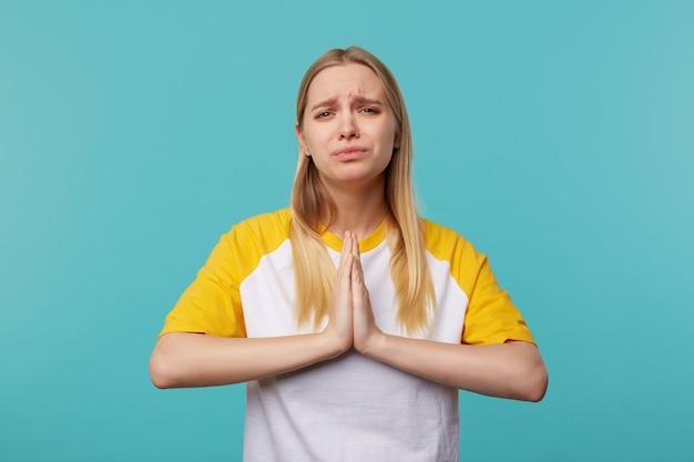 Jammerende jonge vrij langharige blonde vrouw houdt haar handpalmen bij elkaar en fronst helaas wenkbrauwen terwijl ze naar de camera kijkt, geïsoleerd op blauwe achtergrond