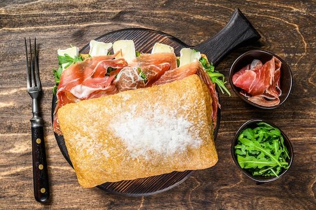 Jamon ham sandwich op ciabattabrood met rucola en camembertbrie. houten achtergrond. bovenaanzicht.