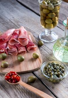 Jamon met kappertjes en olijven op de houten plank
