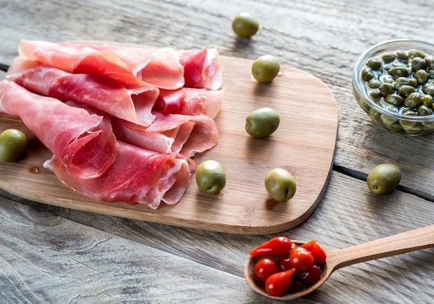 Jamon met kappertjes en olijven op het houten bord