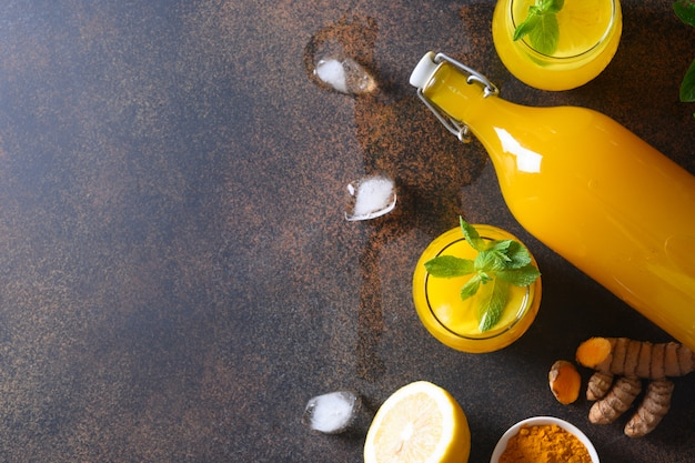 Jamu indonesische kruidendrank met natuurlijke ingrediënten kurkuma, gember op bruine achtergrond. ruimte voor tekst.