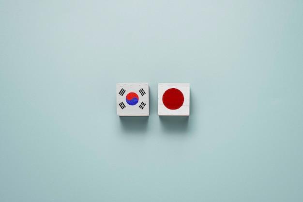Japan en zuid-korea vlagafdrukscherm op houten blokblokjes op blauw.