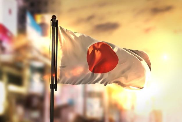 Japan vlag tegen stad wazige achtergrond bij zonsopgang backlight