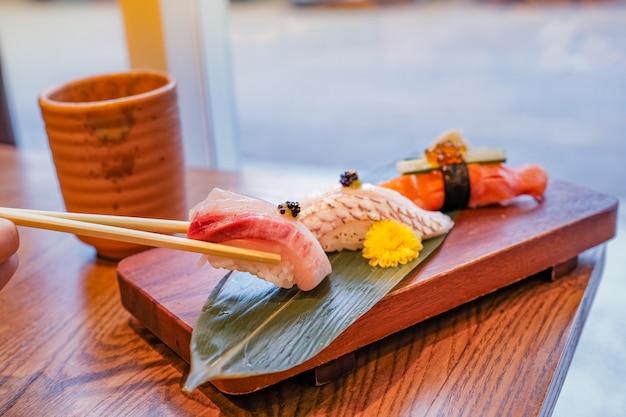 Japans eten, een set sushi op een rechthoekig houten bord, een stuk werd geplukt met stokjes en een kopje groene thee naast