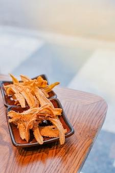 Japans eten, gebakken visgraten in kleine plaat op houten tafel