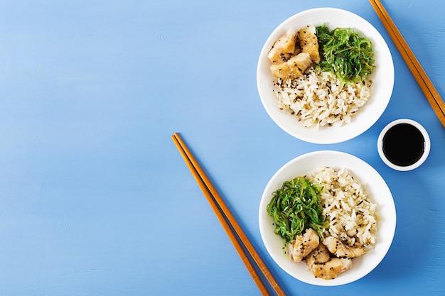 Japans eten. kom rijst, gekookte witte vis en wakame chuka of zeewiersalade