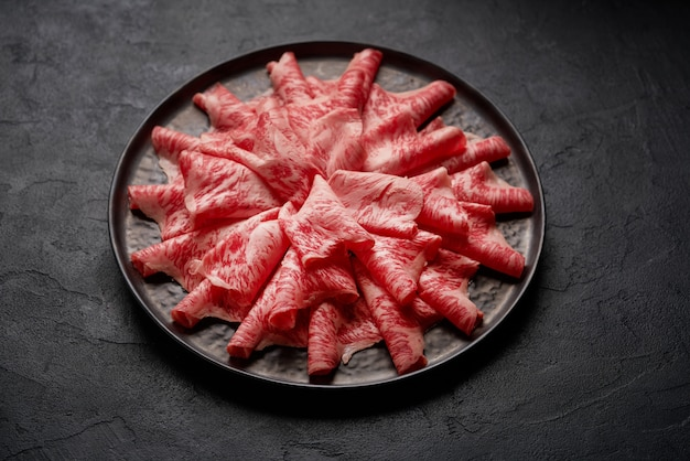 Japans kobe-rundvlees dat op plaat wordt gesneden die op shabu shabu wordt voorbereid