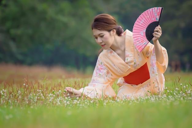 Japans meisje dat in traditionele kleren op het park zit