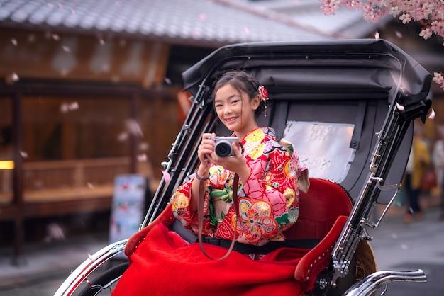 Japans meisje neemt een foto door haar camera en zit op traditionele traier