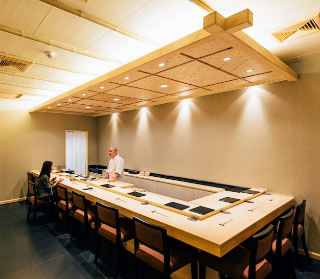 Japans omakase-restaurant dat grotendeels met hout is ingericht. chef-kok die in keukenteller kookt en direct aan klant dient.