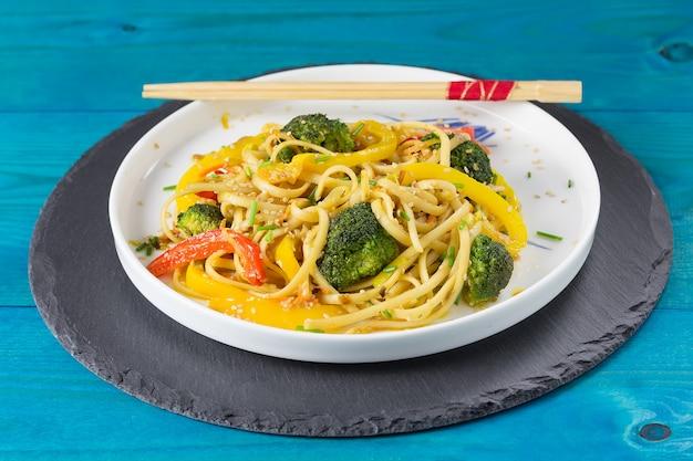 Japans roerbak udonnoedels met groenten op een witte plaat