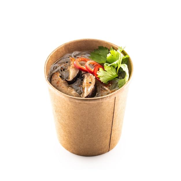 Japanse aziatische soep in een kopje gerecycled papier geïsoleerd op een witte achtergrond. concept van biologische voedselverpakking.