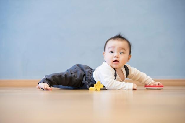 Japanse baby kruipen op de houten vloer in de kamer