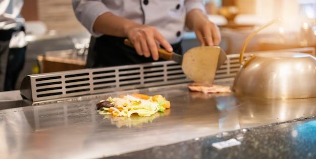 Japanse chef-kok die vlees in teppanyakirestaurant kookt