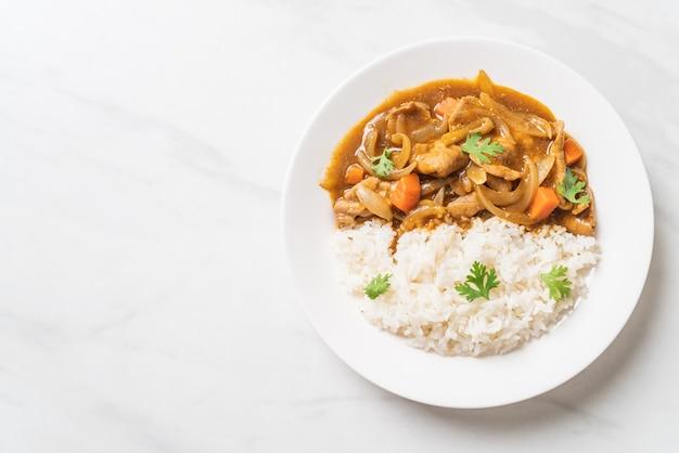 Japanse curryrijst met gesneden varkensvlees, wortel en uien