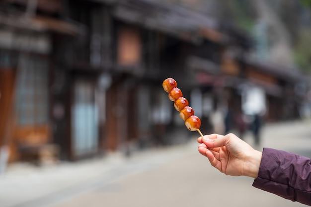Japanse dessertrijstknoedels op stokjes met zoete sojasaus, mitarashi dango genaamd, met narai-juku bewaard gebleven historische poststad. beroemd snackvoedsel