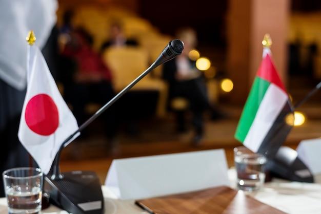 Japanse en emirati-vlaggen op een tafel met microfoon in een internationale conferentie