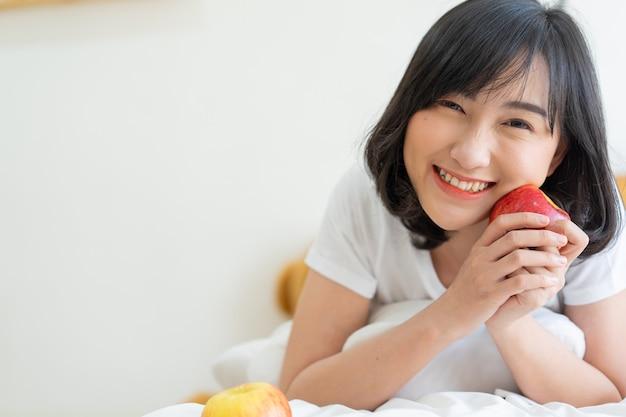 Japanse glimlach van het tienermeisje met wellness en houdt rode appel op gezicht voor gezond levensstijlconcept