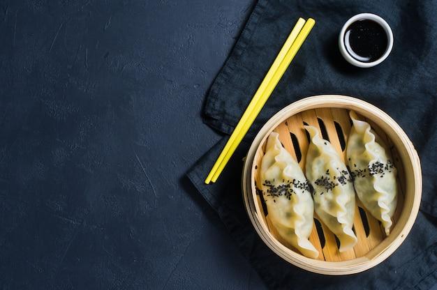 Japanse gyoza in een traditionele stoomboot, gele eetstokjes