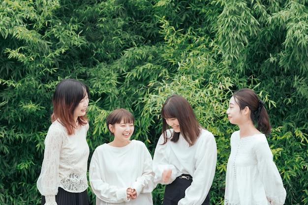 Japanse jonge vrouwen die witte overhemden dragen en in het park chatten