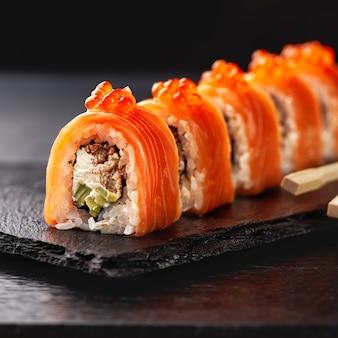 Japanse keuken. zalmsushi rollen in eetstokjes op een stenen plaat over betonnen ondergrond.