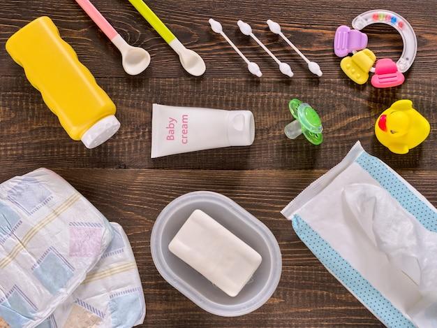 Japanse luiers, vochtige doekjes, zeep, babypoeder, crème, titer, wattenstaafjes, lepels, fopspeen en eendje op houten achtergrond
